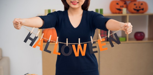 lady holding a sign that reads - HALLOWEEN