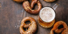 Glass of lager beer with traditional salted pretzels over old dark wooden background. Top view with space for text. Oktoberfest theme