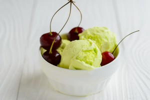 Pictachio ice cream in white bowl with cherry