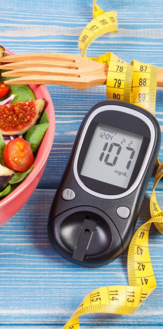 Fruit and vegetable salad and glucometer with result of sugar level, concept of diabetes, slimming and healthy nutrition