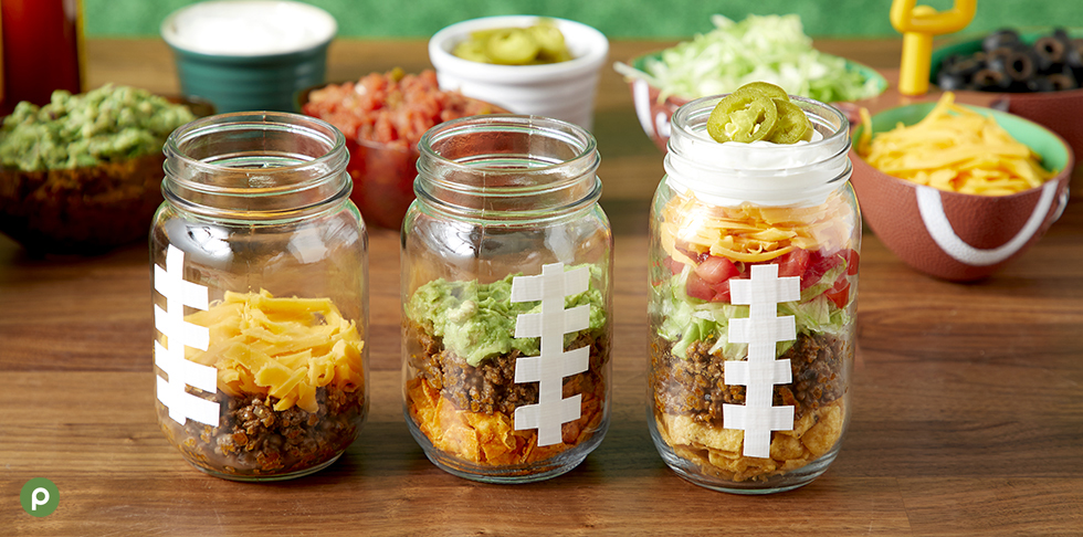 Three mason jars filled with taco ingredients including chips, guacamole, ground beef, cheese, lettuce and tomatoes in front of additional taco ingredients.