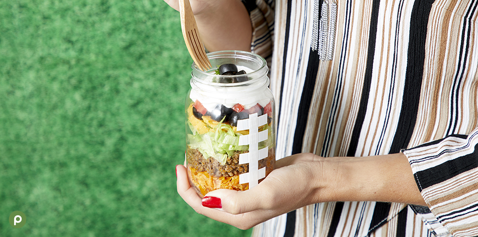Person holding mason jar walking taco filled with chips, ground beef, lettuce, black olives, sour cream, cheese and tomatoes.