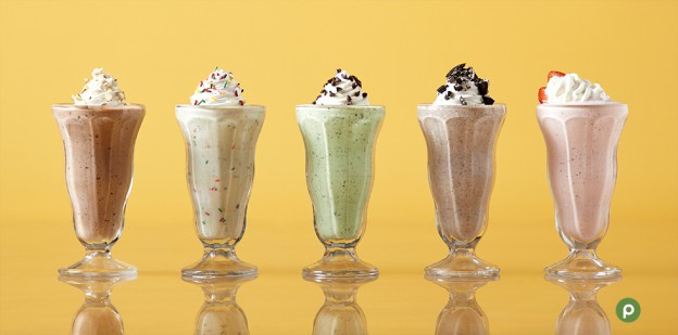 "alt= ""Heavenly hash, birthday cake, mint chocolate chip, cookies and cream, and strawberry milkshakes lined up on yellow background in milkshake glasses"""