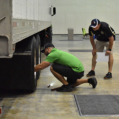 Publix truck driver checking wheel on Publix trailer at Truck Driving Championship.