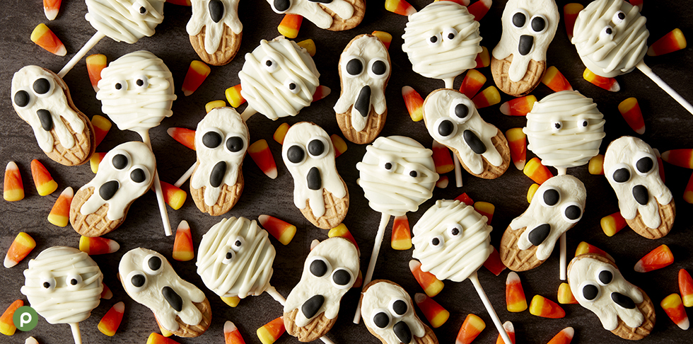 Candy corn, ghost decorated nutter butters, mummy decorated sandwich cookies on sticks