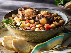 Publix Aprons Oxtail Stew with Chickpeas recipe served in a bowl on napkin with bread.