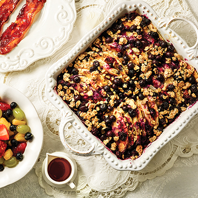 Blueberry pancake casserole in dish on table with side of bacon and fruit)