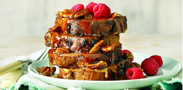 """alt= """"French toast topped with raspberries and maple syrup on blue plate."""""""