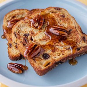 """alt= """"Publix aprons cinnamon swirl French toast topped with pecans and maple syrup on blue plate."""""""