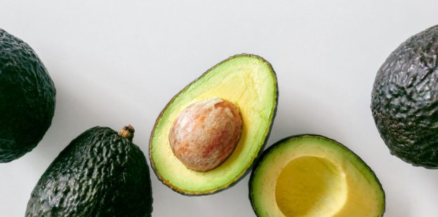 "Alt= ""four avocadoes on white background with one avocado split open"""