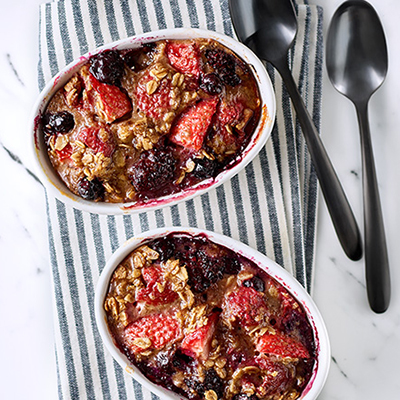 Berry oat bake in casserole dish on table with silverware