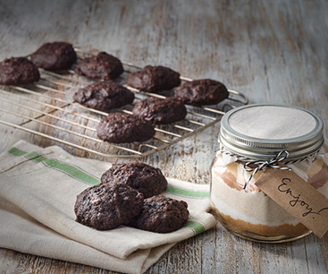 "Alt= ""chocolate banana cookies on cooling rack with a container of the cookie mix to the side"""