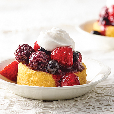 raspberries, strawberries and whipped cream on shortcake on a circular white plate on a white lace surface