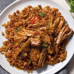 Chuck roast shredded with onions, celery and peppers over jambalaya rice and mixed in broth on white plate.