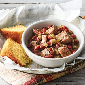 Pork chunks, peppers, celery, onions and red beans in white bowl with side of cornbread.