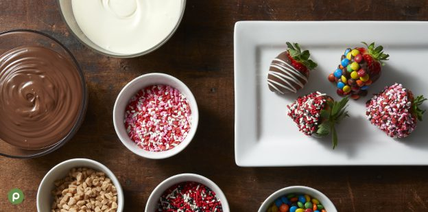 4 chocolate covered strawberries on a white rectangular plate next to bowls of melted milk and white chocolate and sprinkles and nuts