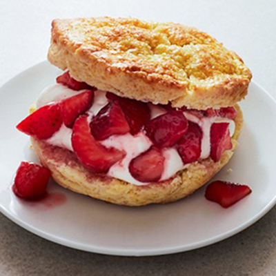Strawberries and whipped cream sandwiched between two pieces of shortcake on a circular white plate