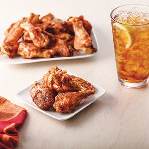 Mardi Gras wings on small white plate in front of Mardi Gras wings on a larger white plate with glass of tea with lemon to the right side. Burgundy cloth napkin to the left.