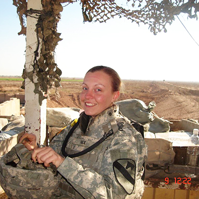 woman in army uniform smiling at camera with dessert environment behind her