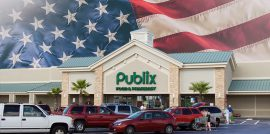Publix store with cars in parking lot in front and American flag background behind the store