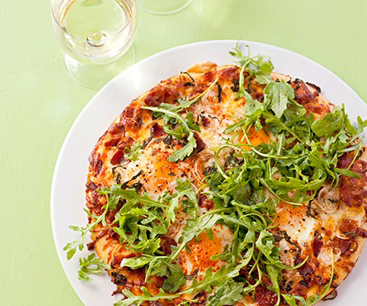Pizza topped with baked eggs, cheese and arugula