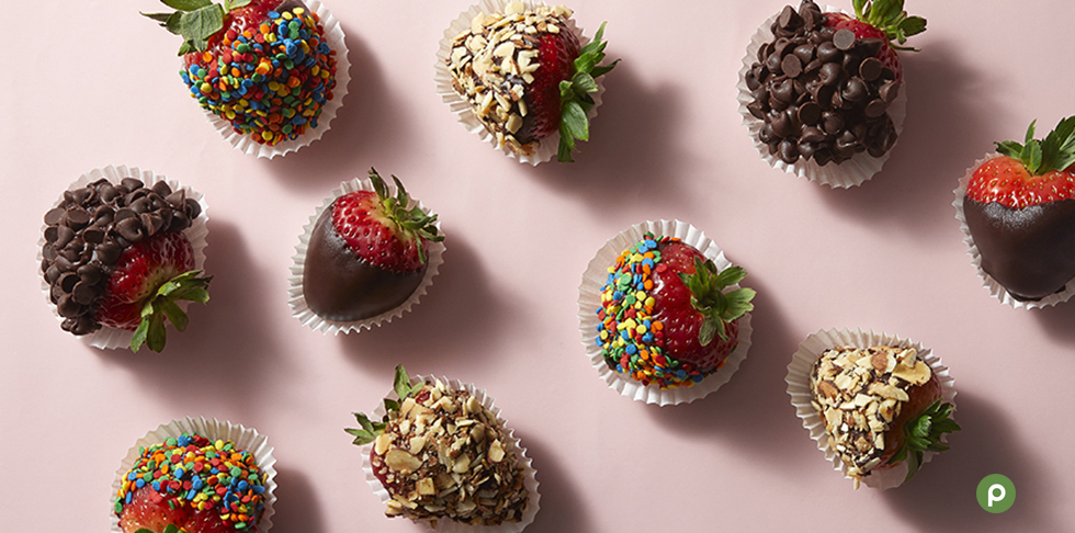 Ten strawberries coated in sprinkles, almonds, chocolate or chocolate chips in miniature white cupcake wrappers on a pale pink background