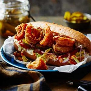 Sandwich roll filled with fried shrimp, lettuce, tomato, onion and pickles on blue plate.