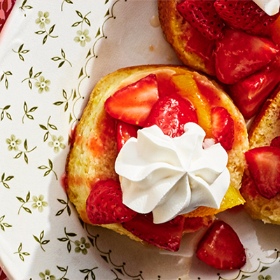 Strawberries and oranges topped with whipped cream on shortcake, sitting on a floral plate
