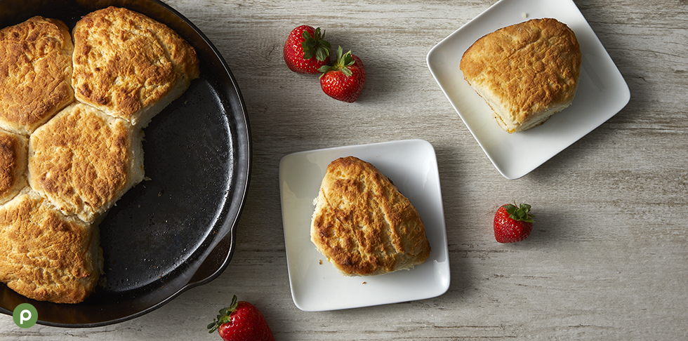 5 biscuits in a baking pan and 2 biscuits each on a square white plate with a few scattered strawberries on a light wood background