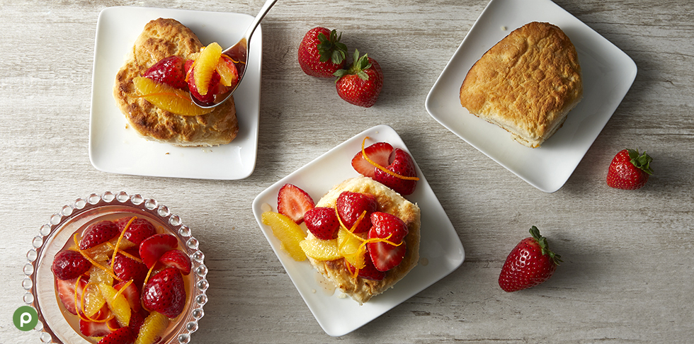 3 biscuits each on a white square plate. Two are topped with strawberries, oranges and orange zest on a light wood background