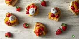 strawberries, oranges, orange zest and whipped cream on top on biscuits on a pale wood background