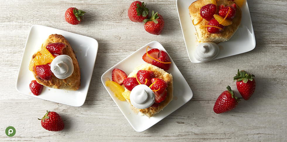 3 biscuits each on a square white plate topped with strawberries, oranges and orange zest and whipped cream with strawberries scattered on a light wood background