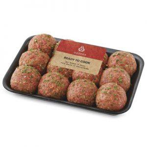 Raw meatballs sprinkled with seasoning in black packaging tray.