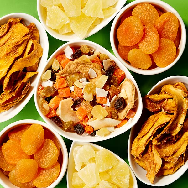 Publix dried fruit in white bowls on bright green surface.