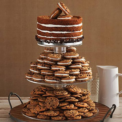 """Alt= """"One tier of chocolate chip cookies and one tier of chocolate chip cookies with icing in the middle with an iced cookie cake as the top tier."""
