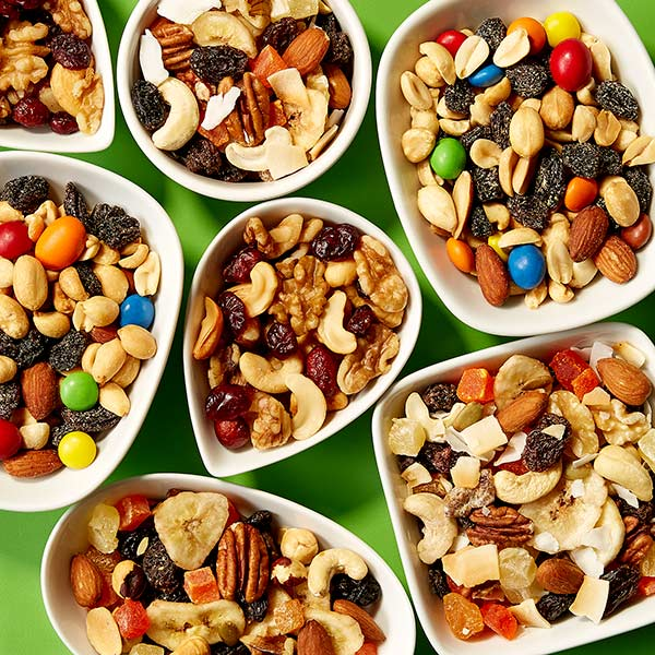 Produce department trail mix, sunburst mix, cranberry nut mix and raisin mix in white bowls on bright green surface.