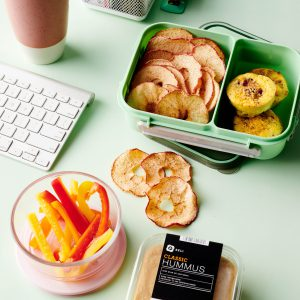 """Alt= """"Publix classic hummus inside container, multicolored sliced bell peppers in glass jar, sliced apple chips and baked eggs in container, office supplies, stapler and coffee mug on blue background."""""""