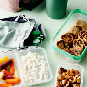 """Alt= """"snack box will cottage cheese and multicolored carrots, mixed nuts in a snack box, peanut butter and grape rollups in a snack box, green utensils inside a polka dot blue napkin, teal water bottle and pink lunchbox on blue background."""""""