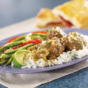 Meatballs in savory gravy with lime, asparagus and red peppers over white rice on blue plate.