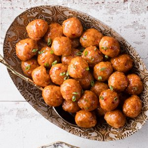 Chicken meatballs with brown sugar glaze piled into a bowl on white wood surface.