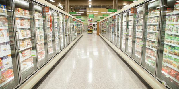 Frozen food aisle with frozen foods in cases on each side of aisle with lights on to show products.
