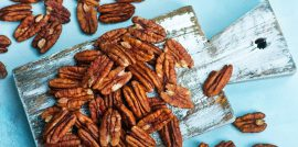 Pecans scattered on a white wood cutting board on a light blue background