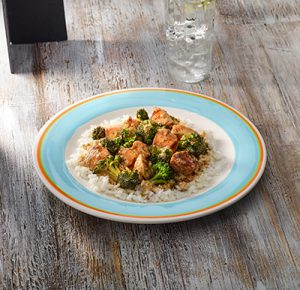 Bronzed chicken and broccoli served over rice with yogurt sauce on blue rimmed plate.