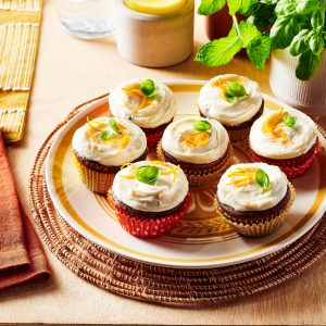 Carrot cake cupcakes with cream cheese frosting topped with shaved carrots and basil