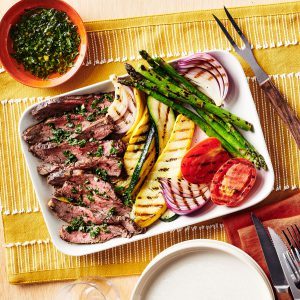 Sliced steak on plate with grilled zucchini, squash, onions and tomatoes