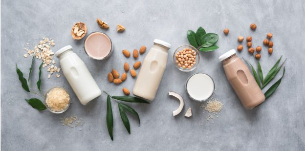 Three bottles of milk surrounded by leaves and nuts on a slate grey background.
