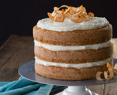 Tri-layered coconut cake topped with carrot shavings