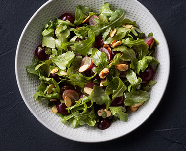 Salad topped with grapes and almonds