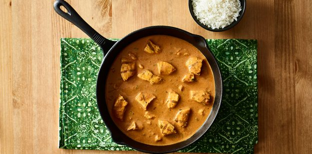 Greenwise frozen tikka masala in a skillet on a green patterned cloth next to a small bowl of white rice