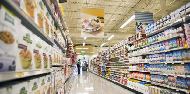 Bright grocery store aisle with shelves filled with products and man stocking shelves